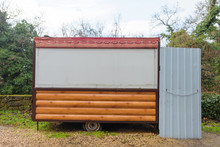 Carriage Trailer On Wheels. Trading Trailer For Street Trading. Shop On Wheels. Shop-wagon Covered With Wooden Beams. Kiosk. Plants With Green Foliage. Cloudy Sky.