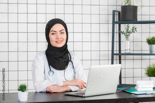 Fotomural  Muslim female doctor writing report on her working desk