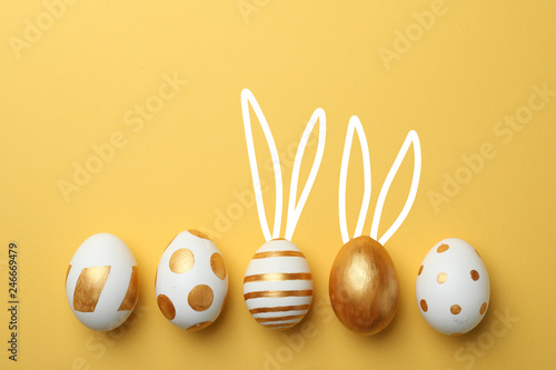 Photo Decorated Easter eggs and cute bunny's ears on color background, top view with s