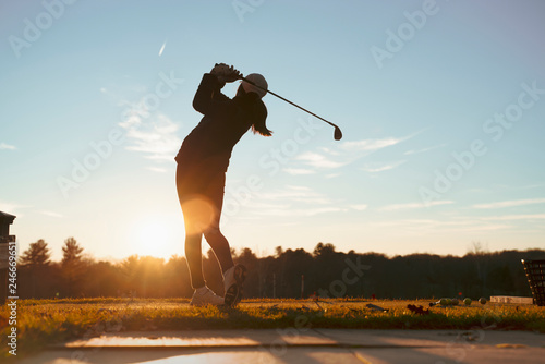 Fotografía  Young junior golfer practicing in a driving range with beautiful sunset light in winter
