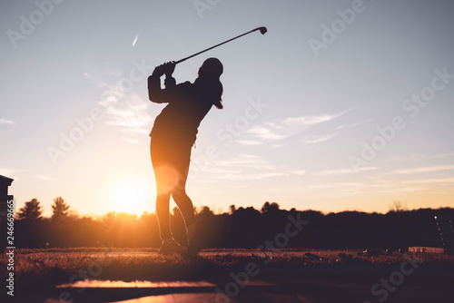 Young junior golfer practicing in a driving range with beautiful sunset light in winter Fototapete