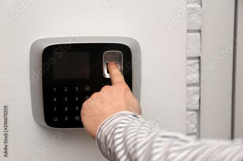 Fotobehang Historisch geb. Man scanning fingerprint on alarm system indoors, closeup