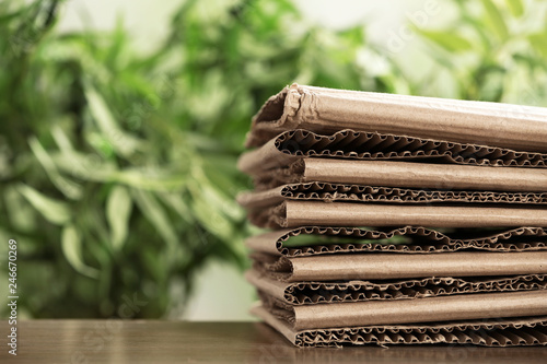 Stack of cardboard for recycling on table against blurred background. Space for text