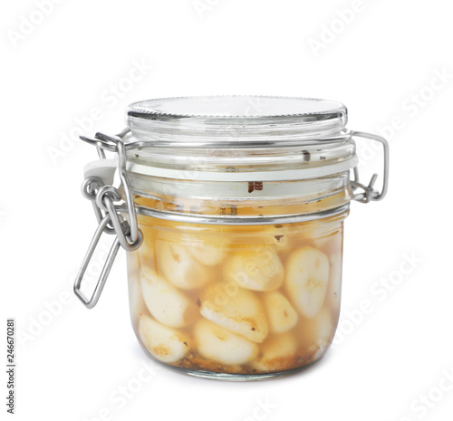 Glass jar with preserved garlic on white background
