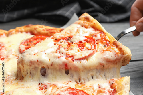 Woman taking slice of hot cheese pizza Margherita on table, closeup