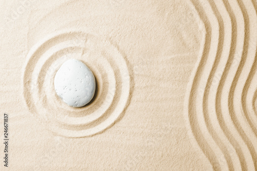 Zen garden stone on sand with pattern, top view. Space for text