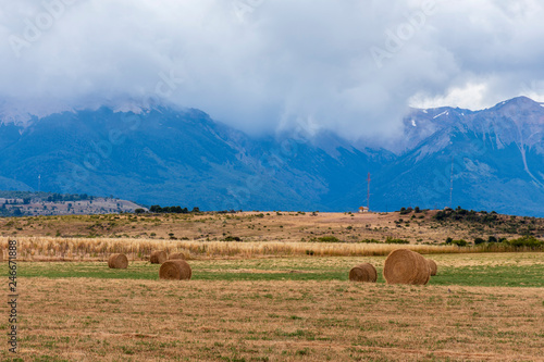Cadres-photo bureau Message inspiré round bales of straw in a Patagonia field against Andes mountains.