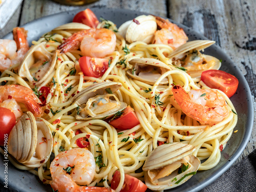 Cooked pasta with seafood clams, shrimps tomato on a plate , spaghetti Fototapet