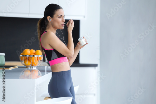 Fotografie, Obraz  Sporty young woman listening to music with mobile phone while eating yogurt in the kitchen at home