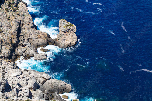 Sea wave breaks on beach rocks landscape.
