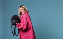 Beautiful Blonde Girl Wearing Pink Coat Holding Black Backpack In Hands