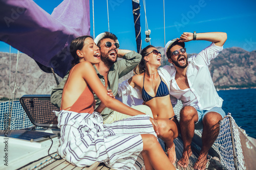 Fototapeta Smiling friends sailing on yacht. Vacation, travel, sea, friendship and people concept obraz