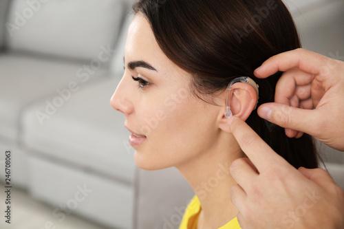 Man putting hearing aid in woman's ear indoors, closeup Canvas Print