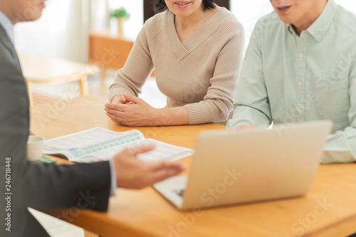 中年夫婦に説明するビジネスマン Fototapeta