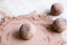 Close Up Image Of Raw Dates, Oats, Linseed And Chia Seed Energy Balls Rolled In Cacao Powder