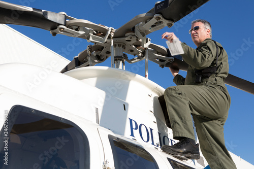 Fotografie, Obraz  Policeman Pilot doing flight check