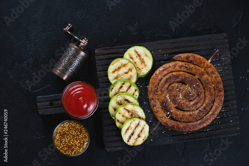 Black wooden serving board with grilled coiled sausage, zucchini slices and dipping sauces. Flatlay on a black stone surface