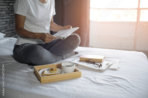 Photo  Happy woman reading a book and relaxing comfortably at home.