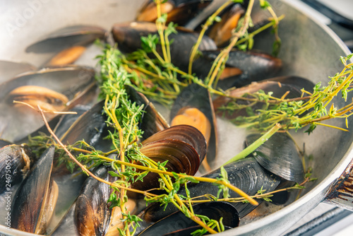 Mussels are cooked in a pan with spices.