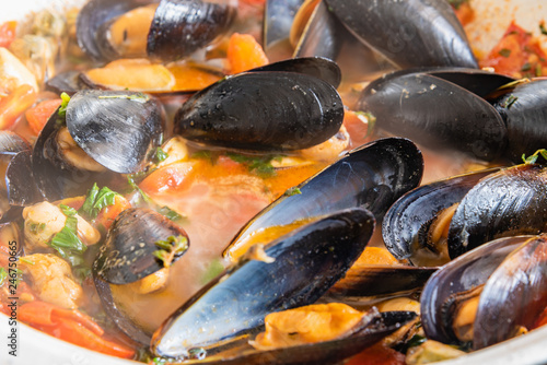 Homemade tasty sauce with mussels and vegetables in a pan.