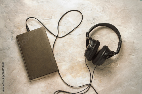 Book and headphones connected to it on a white stone background Canvas-taulu