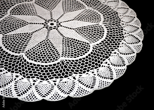 Fotografia, Obraz  A part of isolated crocheted white doily with pattern with cones and arches a black background
