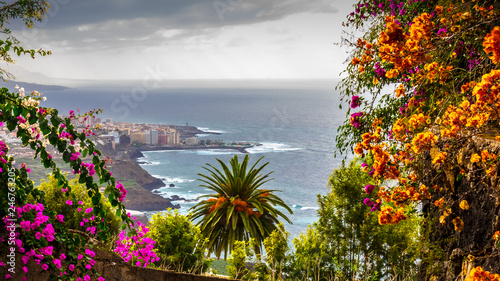 Puerto de la Cruz, Tenerife, Spain - A view of the harbor town of Puerto Cruz, along the coast, a dull day, with dark clouds in October in the fall and colorful flowering plants Fototapeta
