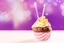 Birthday Cupcake With Two Candle On Pink And Purple Background.
