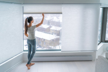 Obraz na PlexiWoman closing cellular shades on apartment window keeping energy and heat indoors with honeycomb blind curtain. Cordless pleated shades in modern home living lifestyle. Interior decor design.