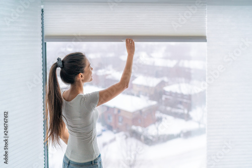 Home blinds window shades woman opening shade blind during winter morning Wallpaper Mural