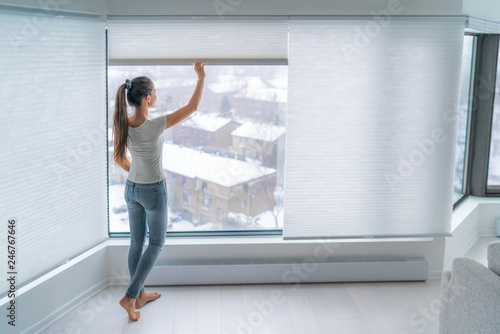 Woman closing cellular shades on apartment window keeping energy and heat indoors with honeycomb blind curtain Fototapet