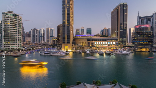 In de dag Kanaal Aerial vew of Dubai Marina with shoping mall, restaurants, towers and yachts day to night timelapse, United Arab Emirates.
