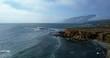 Gorgeous mountain coast line beside calm ocean - aerial tracking shot tilting down