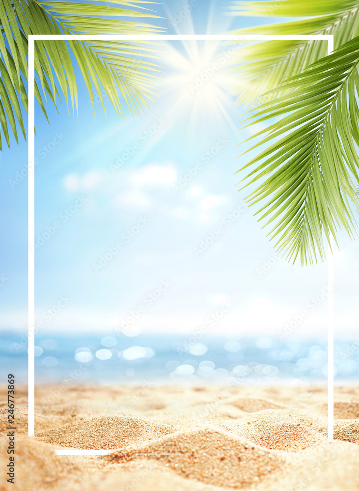 Fototapeta Summer background with frame, nature of tropical golden beach with rays of sun light and leaf palm. Golden sand beach close-up, sea,  blue sky, white clouds. Copy space, summer vacation concept.