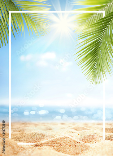 Summer background with frame, nature of tropical golden beach with rays of sun light and leaf palm. Golden sand beach close-up, sea,  blue sky, white clouds. Copy space, summer vacation concept.