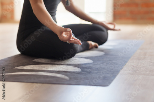 Fotografia  Unidentified young woman yoga instructor meditates In an empty bright room sitting in the lotus position