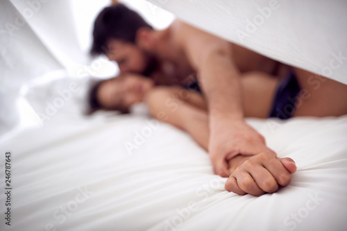 Hands of man and woman lovers having sex on a bed in morning. - 246787643