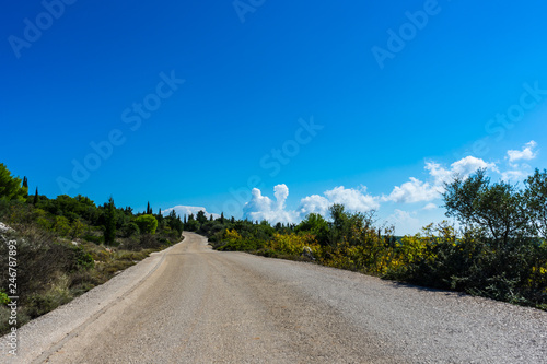 Fotografia  Asphalt road alongside natural landscape and blue sky