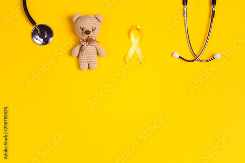 Fotografia Childhood Cancer Awareness Yellow Ribbon with toy bear and stethoscope on yellow background with copy space