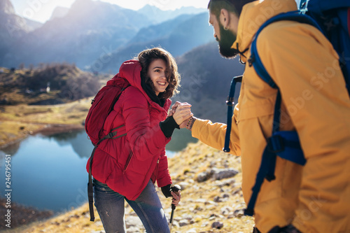 Fotografía  Helping hand - hiker woman getting help on hike happy overcoming obstacle