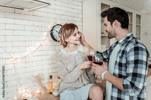 Attractive young dark-haired man in a checkered shirt touching his wifes hair Slika na platnu