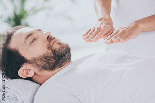 Photo  cropped shot of calm bearded man with closed eyes receiving reiki treatment