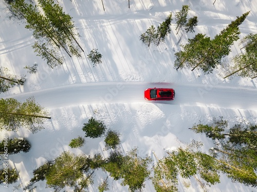 Obraz Aerial view of red car driving through the white snow winter forest on country road in Finland, Lapland. - fototapety do salonu