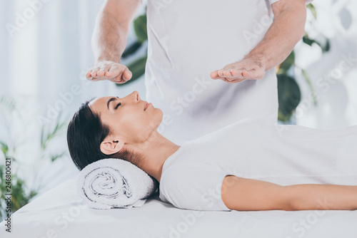 Photo  cropped shot of male healer doing reiki treatment session to young woman with cl