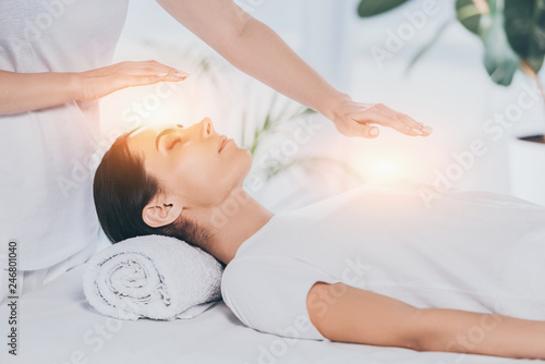 Fotografia  cropped shot of reiki healer doing therapy session to calm young woman with clos