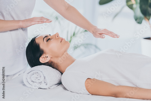 Photo  cropped shot of young woman with closed eyes receiving reiki treatment on head a