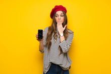 Girl With French Style Over Yellow Wall With Troubled Holding Broken Smartphone