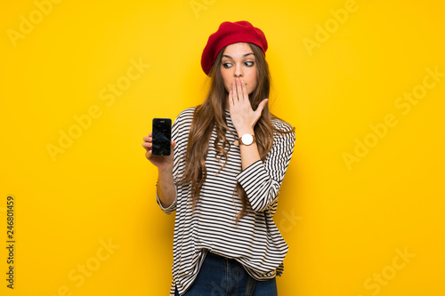 Fototapeta Girl with french style over yellow wall with troubled holding broken smartphone obraz