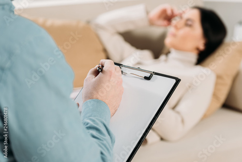 Fotografia, Obraz cropped shot of psychotherapist writing on clipboard and young woman lying on co