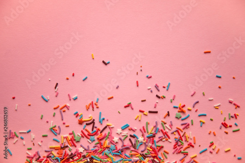 Colorful sprinkles scattered on pink background - 246802659